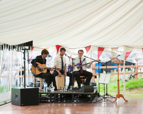 An image showing a live band playing in a marquee for entertainment