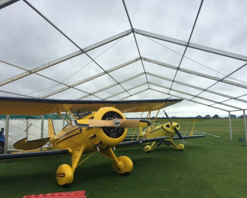 An image of two yellow vintage Aeroplanes held under a structure supplied by Big Top Marquees