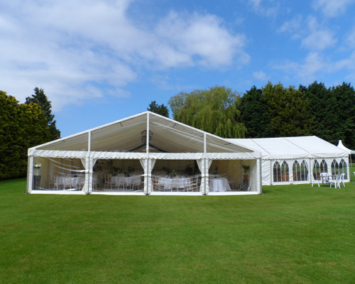 An image of a Floor To Ceiling Window at the side of a large marquee being used for a wedding