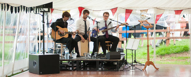 An image of a three man wedding band playing underneath a marquee supplied and installed by Big Top Marquees