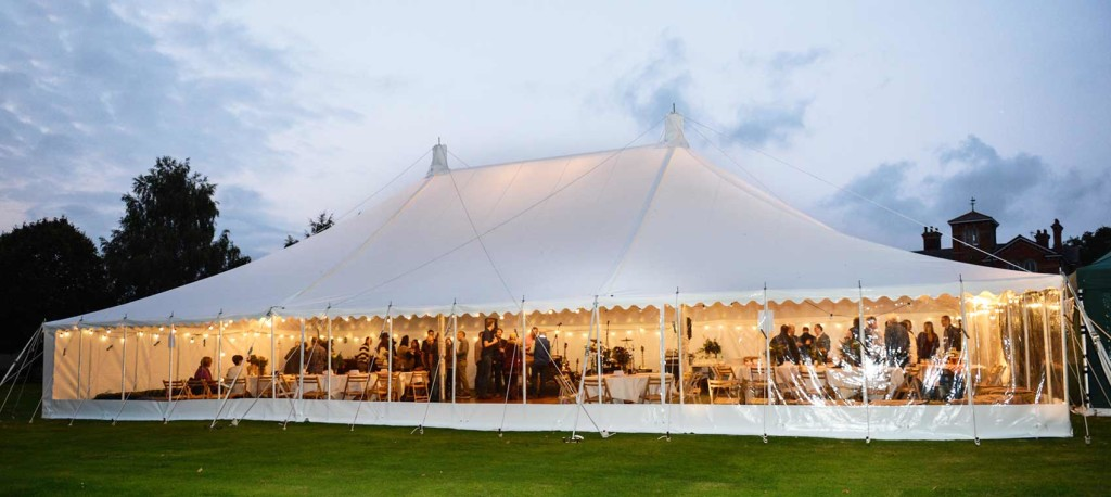 An image of a marquee being used during the evening, lit up with fairy lights.