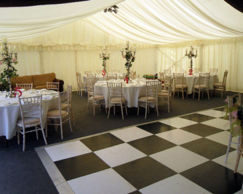 An image showing the inside of a marquee with dance floor and furniture hire in Northampton