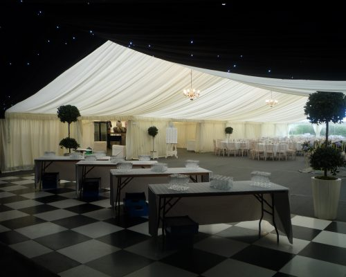 An image of a marquee, half of which has black, starlight draping and half which has white draping, designed and erected by Big Top Marquees.