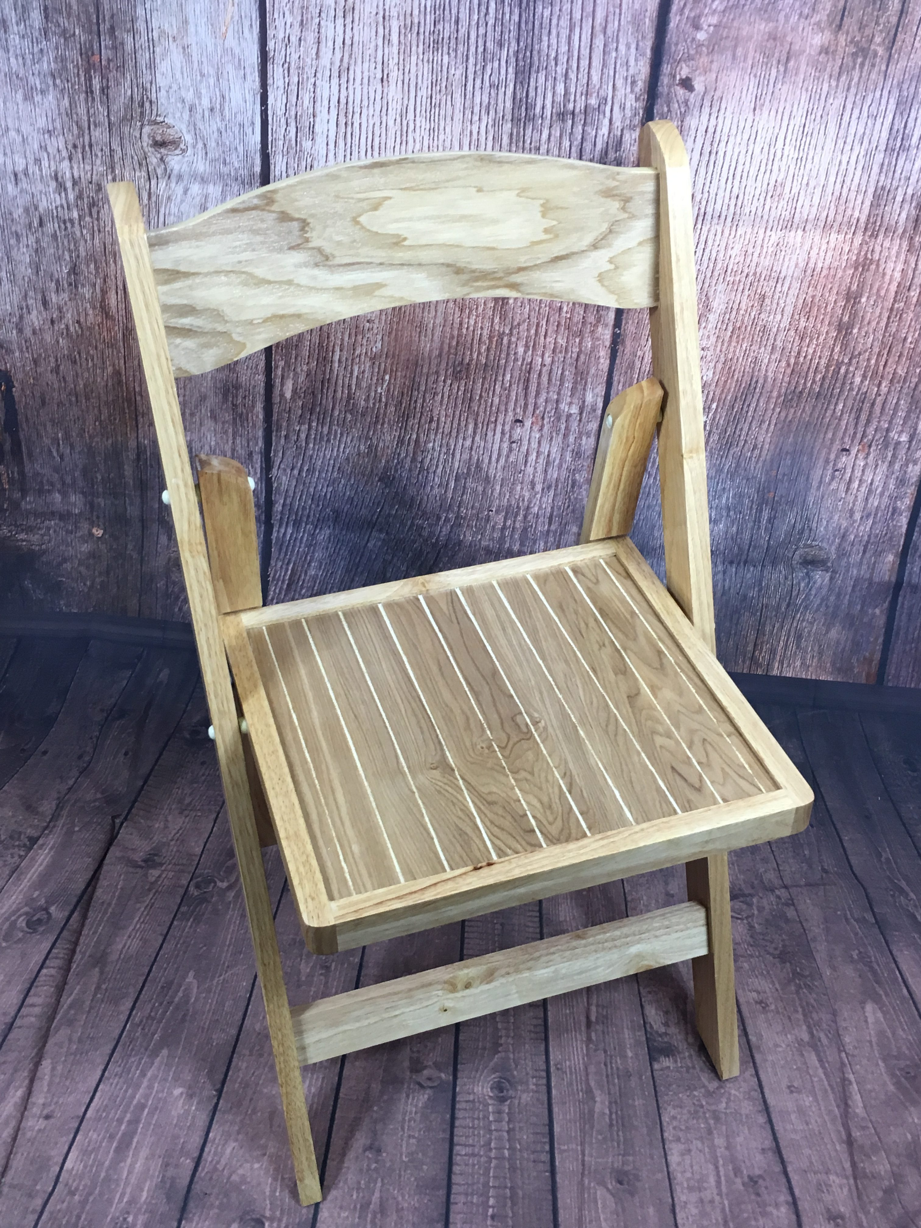 An image of a wooden, folding chair available for hire from Big Top Marquees.