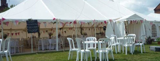An image of a marquee being used for a party with tables and chairs placed outside