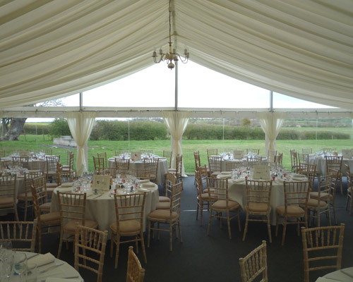 An image of a marquee Interior with multiple round tables dressed for a party wedding
