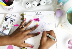 An image of womans hand writing in a full event planning checklist on a desk.
