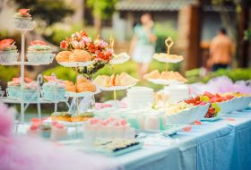 An image of table in a garden filled with food and drink for a spring garden party.