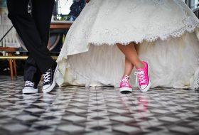 An image of a bride and groom standing together on a chequered floor in their reception venue, showing their Converse trainers.