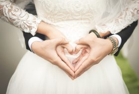 An image of a bride and groom holding their hands in the shape of a love heart.