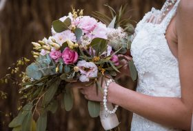 An image of a bride holding a bouquet of flowers at a summer wedding.