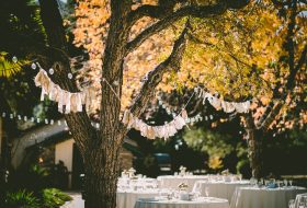 An image of an outdoor wedding setting in autumn, with hanfing bunting and festoon lighting.