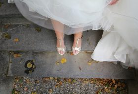 An image of a bride's feet in silver shoes on concrete steps, surrounded by autumn leaves.