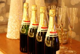 An image of four bottles of champagne and glasses on a table that has been decorated for Christmas.