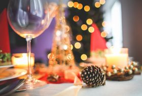 An image of a table at a Christmas party with a glass of wine, a pine cone and a candle.