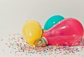 An image of three brighly coloured balloons with confetti.