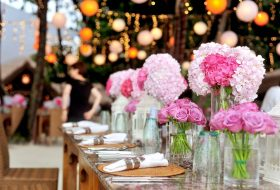 An image of a table inside of a marquee decorated for a wedding in the foreground and marquee lighting and decor in the background.